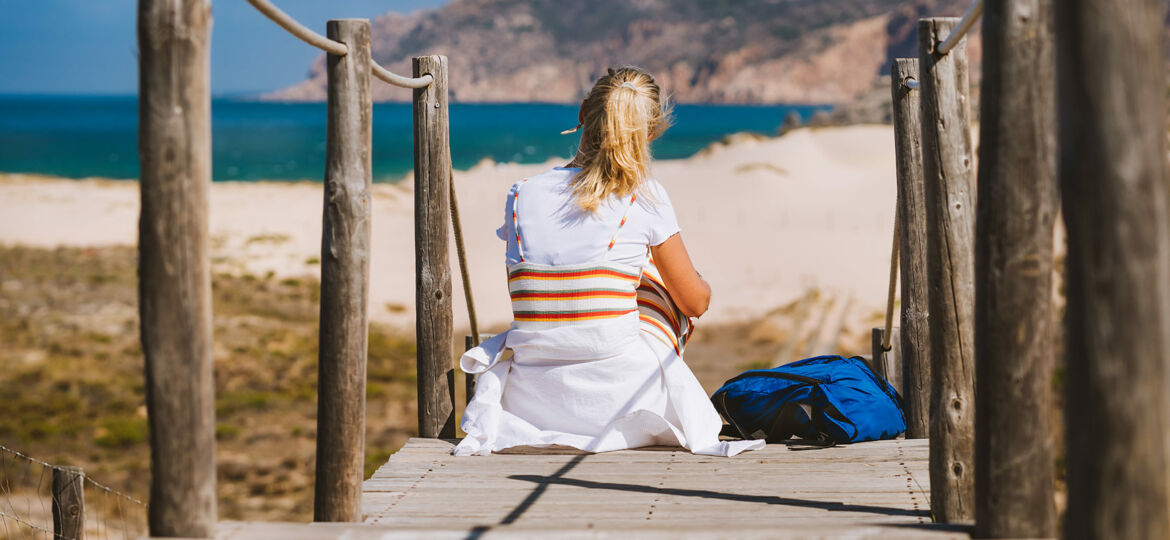 Adult woman sitting on the path to the beach.