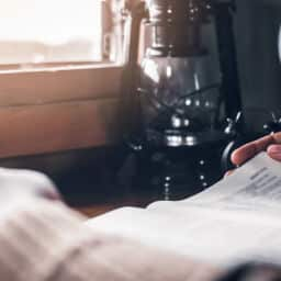 Close-up of a Christian reading the bible on the wooden table in a house.